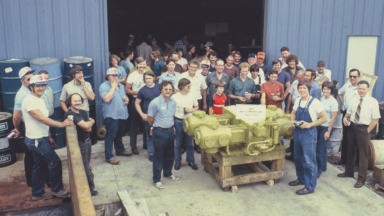 Historic image of employees standing around the 1000th Ariel compressor