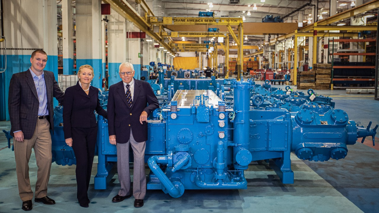 Jim Buchwald, Karen Wright, and Alex Wright stand next to Ariel's 40,000th compressor within their manufacturing complex.
