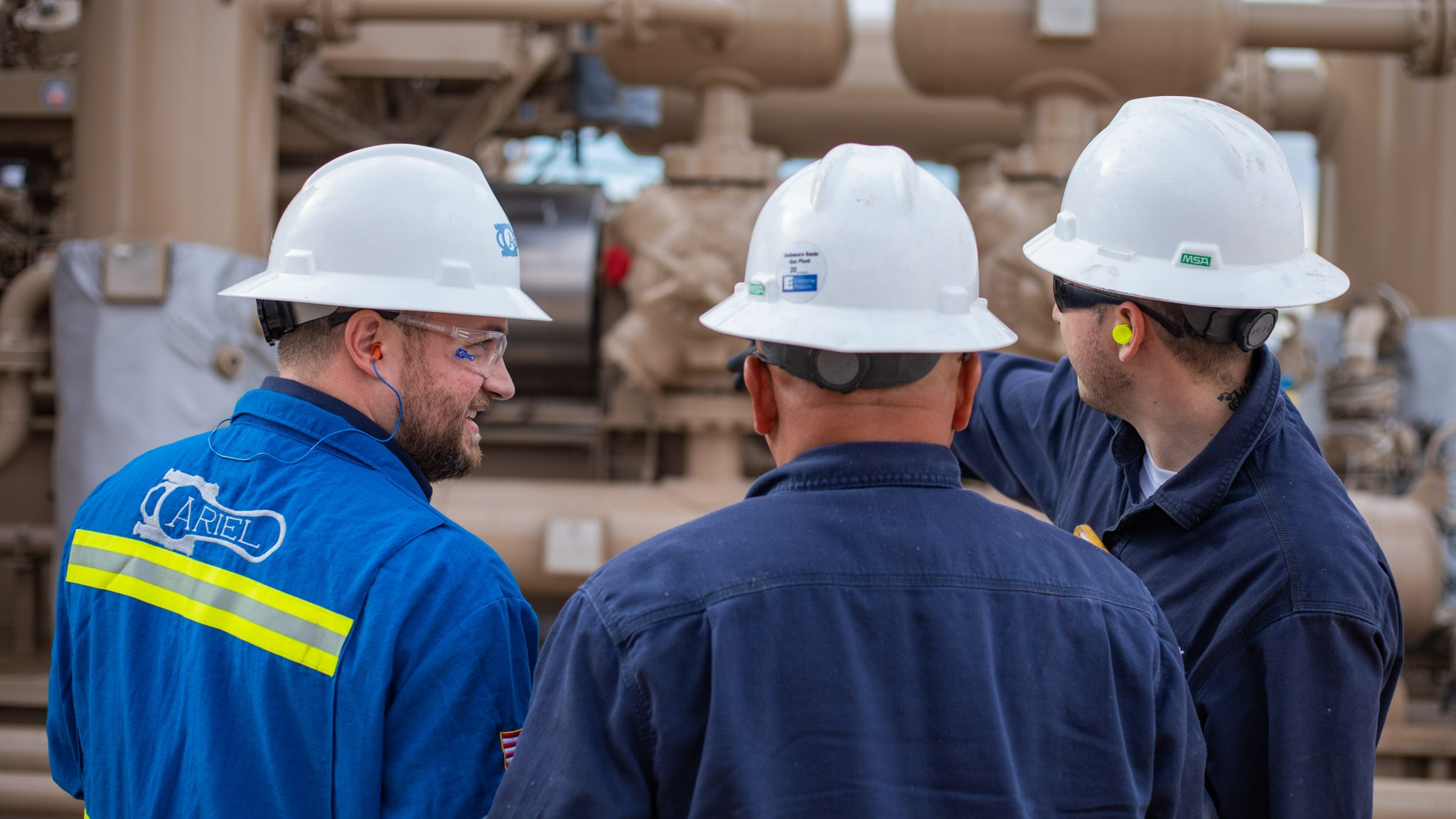 Two mechanics talking to an Ariel technician an the Sandero compressor station in New Mexico