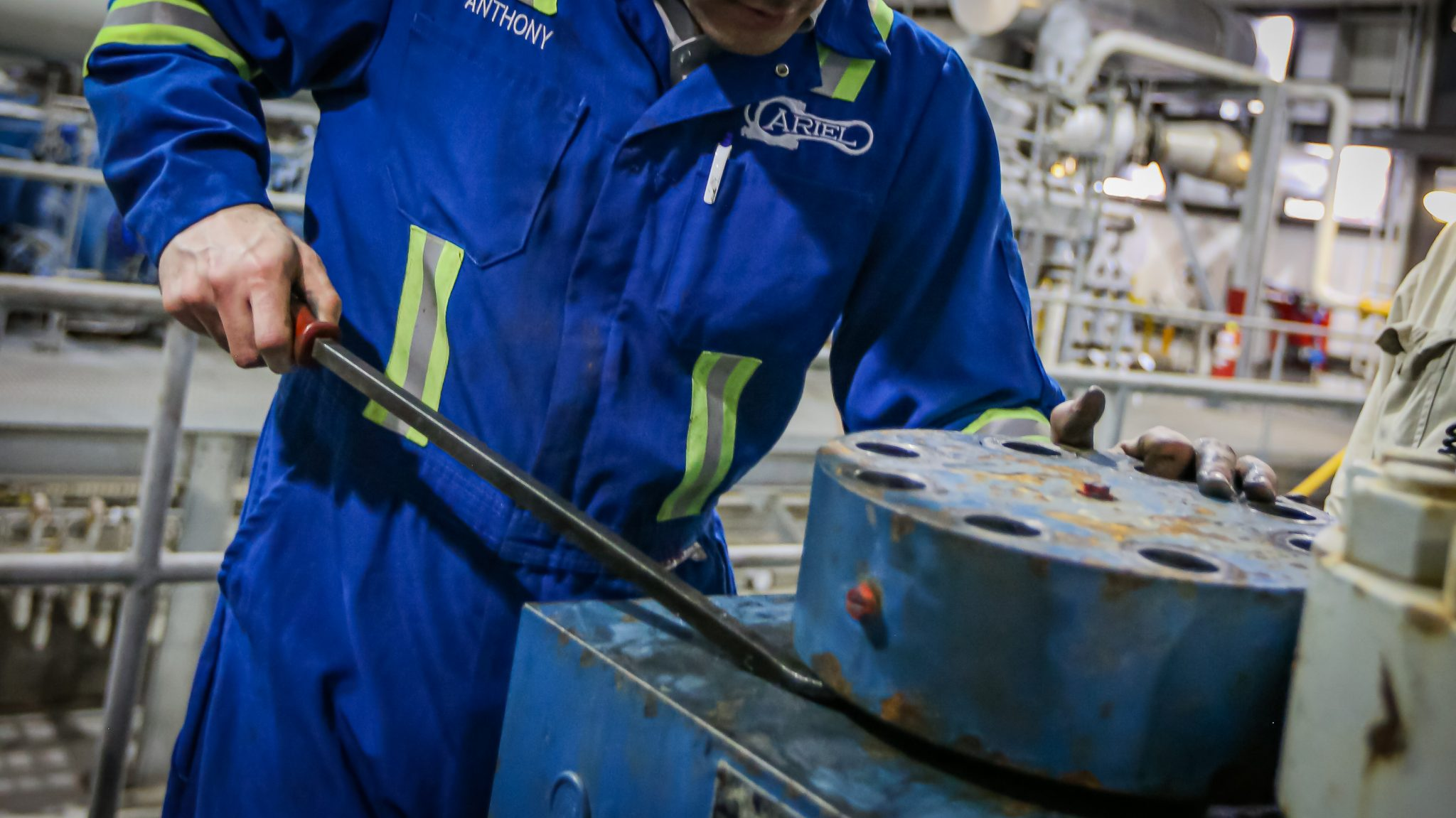 An ariel field technician using a prybar on a high pressure cylinder