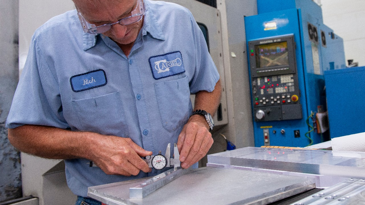 A quality inspector uses a micrometer to ensure a crankshaft is the proper size