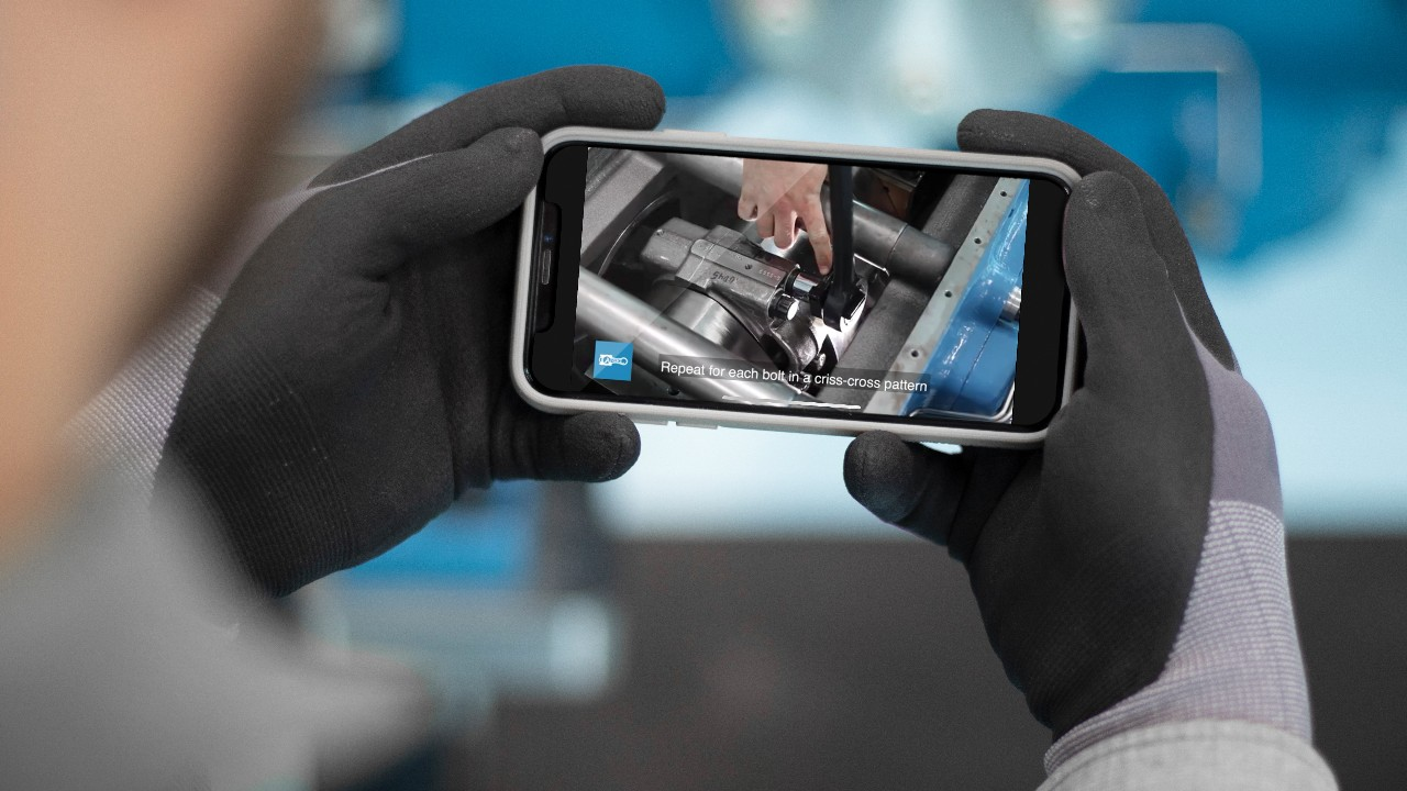 Gloved hands holding a cell phone playing a training video