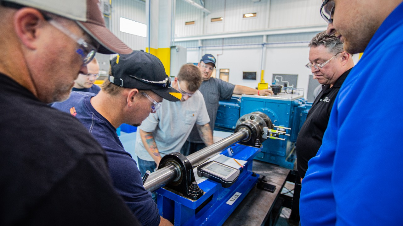 A group mechanics and trainer gathered around a compressor in Ariel's training center
